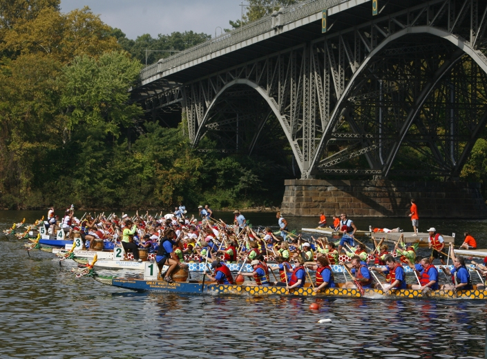 Credit: Photo by R. Kennedy for Visit Philadelphia™ Teams of 20 rowers in colorful Dragon Boats paddle down the Schuylkill River along Kelly Drive for this annual October festival.
