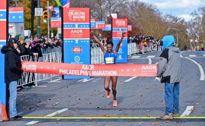 First place female crosses the finish line in the annual Philadelphia Marathon.