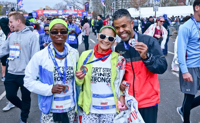 Runners of the Philadelphia Marathon hold up their medals in celebration.